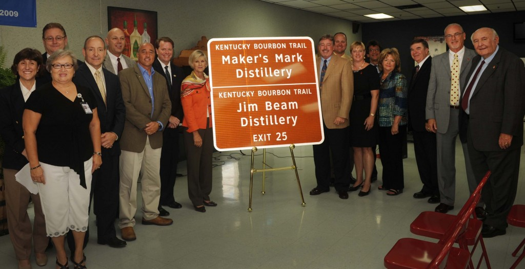 Representatives from the Kentucky Bourbon industry join First Lady Jane Beshear and elected officials in unveiling the first of 17 new Kentucky Bourbon Trail interstate signs. (Left to right): Rep. Linda Belcher; Geri Grigsby (Kentucky Transportation Cabinet); Sen. Jimmy Higdon; Jeff Conder (Beam Global Spirits & Wine); Versailles Mayor Fred Siegelman; KDA President Eric Gregory; First Lady Jane Beshear; Kevin Smith (Maker's Mark); Greg Davis (Maker's Mark); Marnie Walters (Woodford Reserve); Larry Kass (Heaven Hill); Secretary Marcheta Sparrow (Tourism, Arts & Heritage Cabinet); Franklin County Judge-Executive Ted Collins; Jim Rutledge (Four Roses); Jimmy Russell (Wild Turkey).