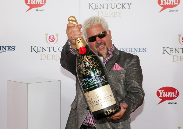 "Guy Fieri signs a limited edition 6 Liter Moet & Chandon Imperial bottle for the brand's philanthropic initiative ""Sign for the Roses"" on the red carpet at the 138th Kentucky Derby on May 5, 2012 in Louisville, Kentucky.  (Photo by Joey Foley/Getty Images for Moet)"