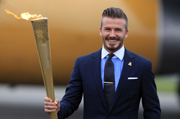 David Beckham holds the London Olympic Flame Torch as it arrives in England