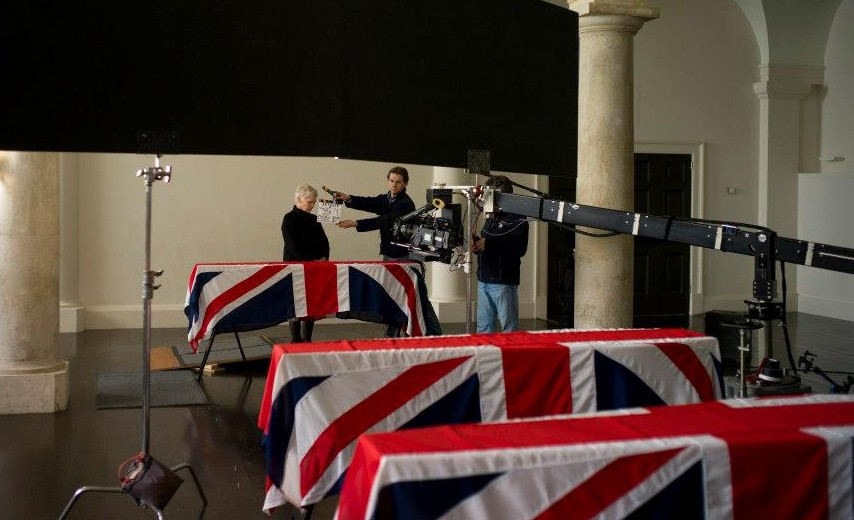 Judi Dench as in M in Skyfall stands behind the coffins of British Soldiers with flags draped in Union Jack Flags. This Bond is Judi Dench's last role as M