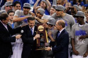 Kentucky head coach John Calipari and Kentucky President Eli Capilouto hold the trophy after the Wildcats defeat the Kansas Jayhawks, 67-59, in the national championship game.