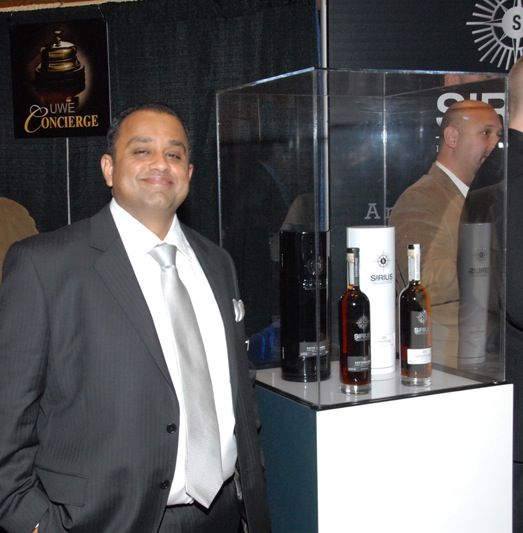 Mahesh Patel, Founder and C.E.O. of Universal Whisky Experience stands nest to his own line of Intrepid Whisky Purveyors