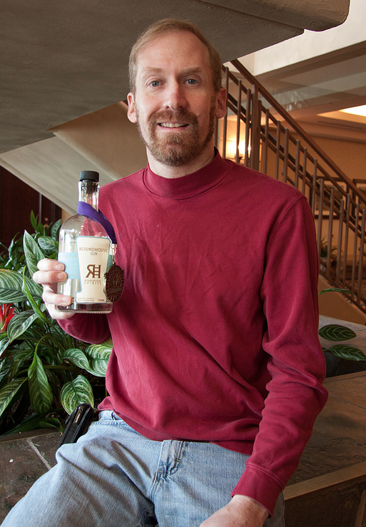 Ted Palmer, Distiller and Owner, poses with his Double Gold Medla winning for his Roundhoues Gin